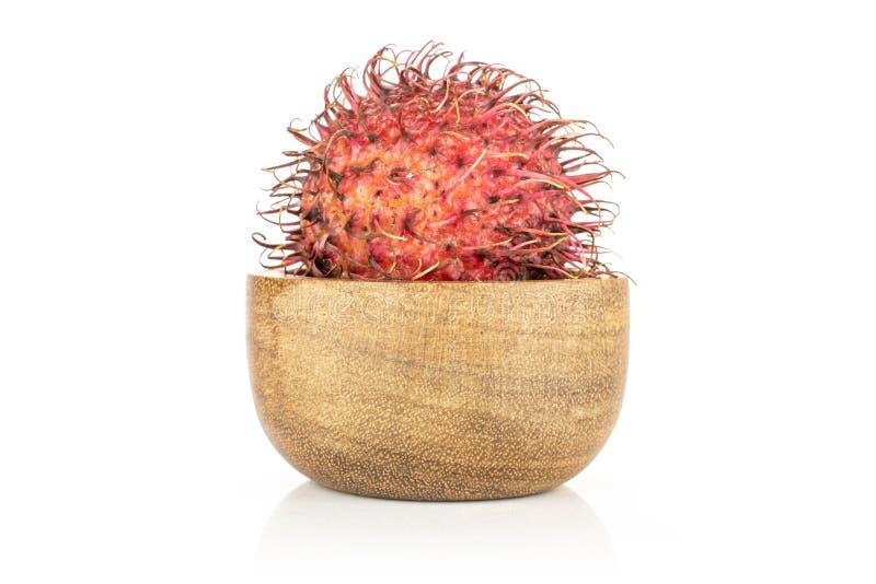 Fresh red rambutan isolated on white. One whole unpeeled fresh red rambutan in wooden bowl isolated on white background royalty free stock photo