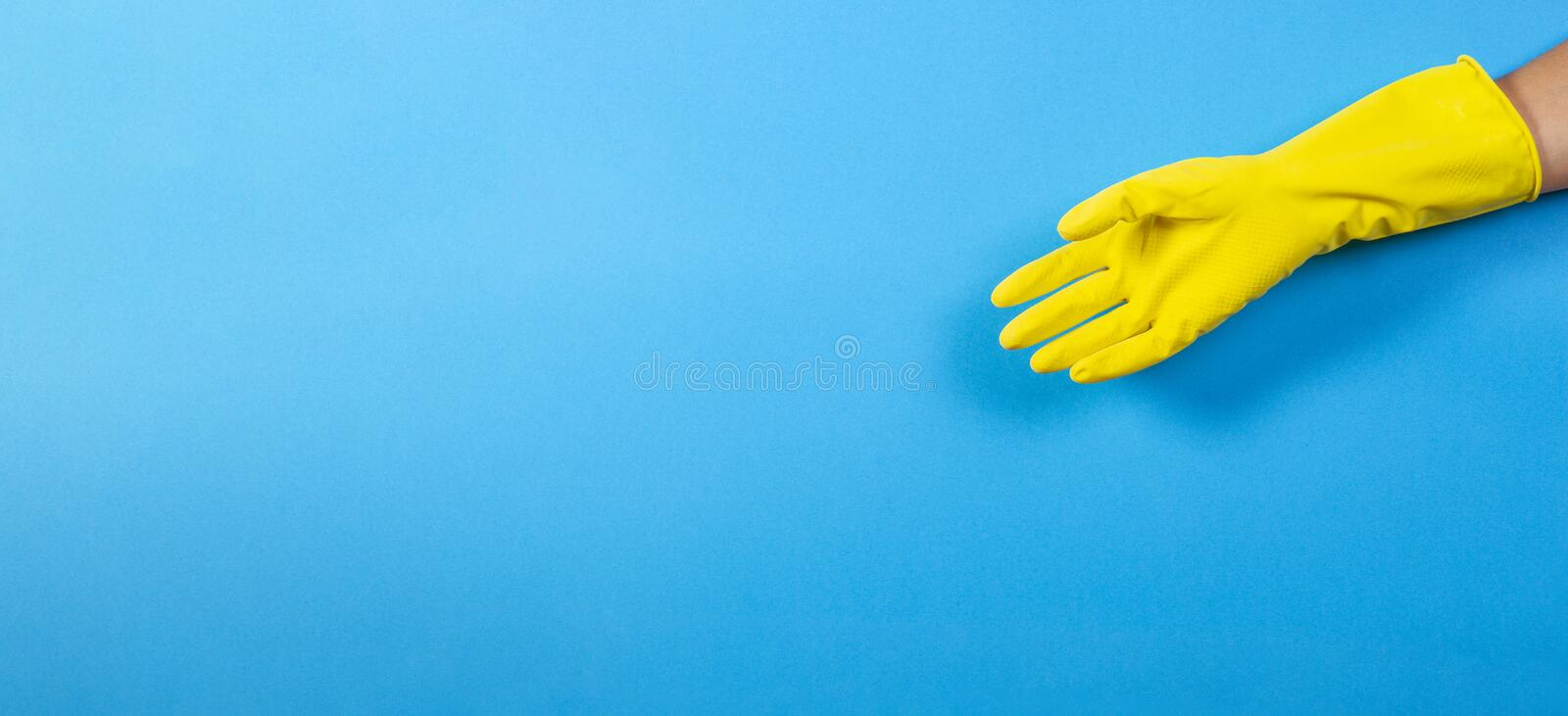One woman hand in yellow rubber glove over blue background stock photo