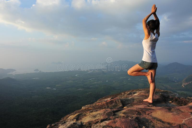 Woman practicing yoga at mountain peak cliff edge. One woman practicing yoga at mountain peak cliff edge stock image