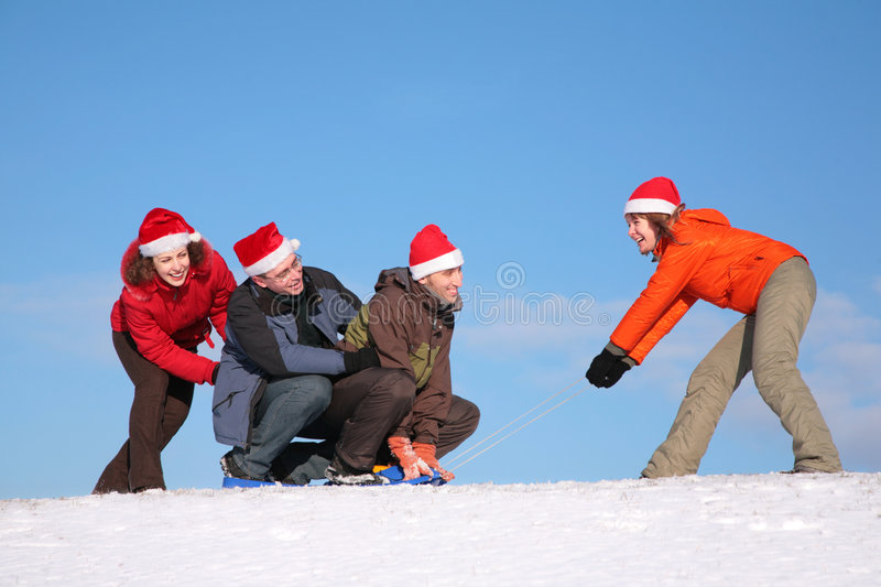 One Woman Pull Two Men On Sled Stock Photos