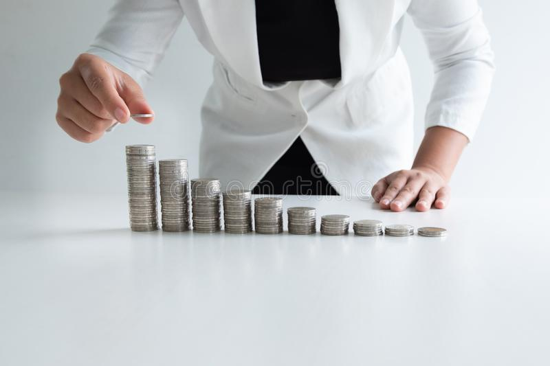 One woman putting coin on growth coins graph in white suit, step up growing business to success and saving for retirement concept royalty free stock images