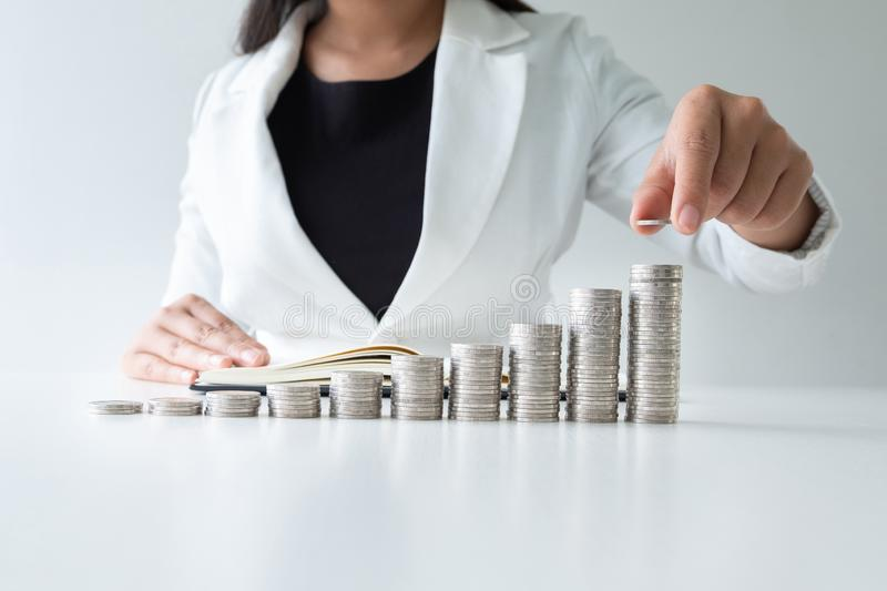 One woman putting coin on growth coins graph in white suit,step up growing business to success and saving for retirement concept stock photography