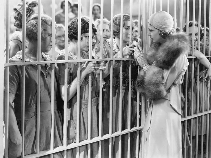 One woman standing in front of a jail talking with a group of women royalty free stock photo