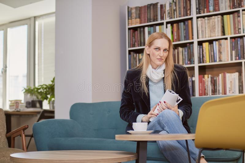 One woman, 40 years old, holding magazine, sitting in book store, book shop, library, shelf full with books behind out of focus stock photos