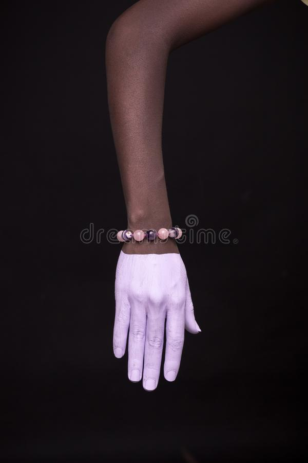 One woman hand, african american painted hand skin, black background, jewelery bracelet. One women hand, african american painted hand skin, black background stock image