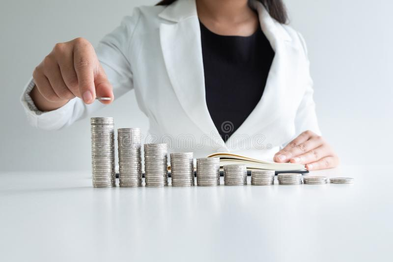 One woman putting coin on growth coins graph in white suit, step up growing business to success and saving for retirement concept stock image