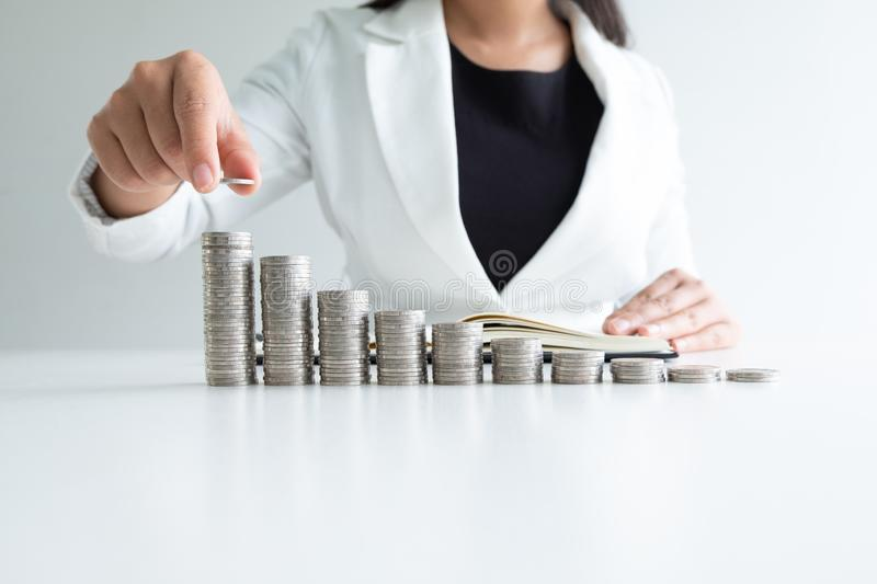 One woman putting coin on growth coins graph in white suit, step up growing business to success and saving for retirement concept stock photo