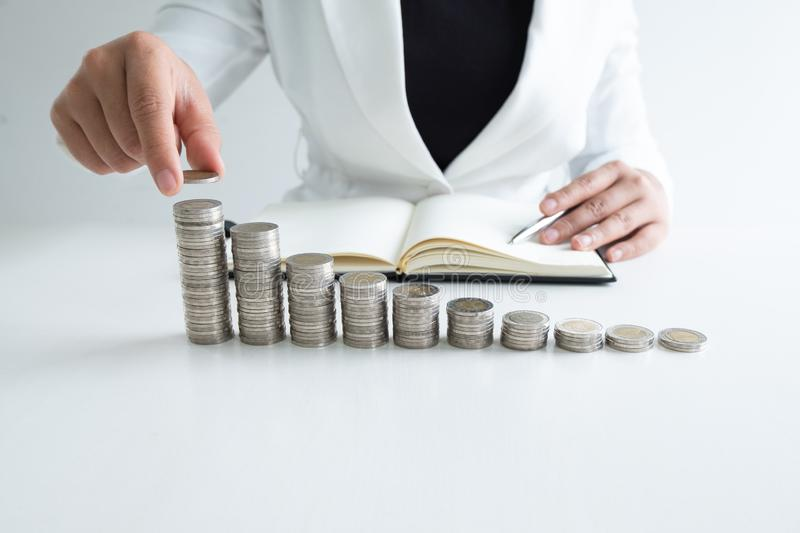 One woman putting coin on growth coins graph in white suit, step up growing business to success and saving for retirement concept royalty free stock photography