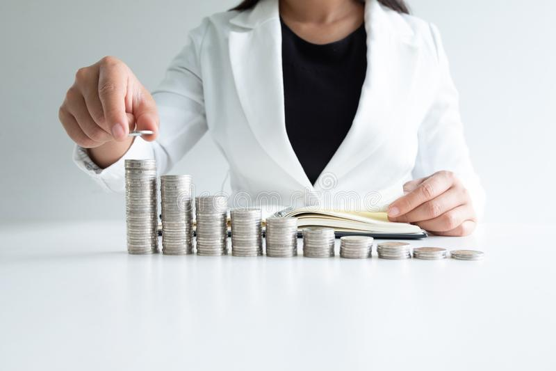 One woman putting coin on growth coins graph in white suit, step up growing business to success and saving for retirement concept royalty free stock image
