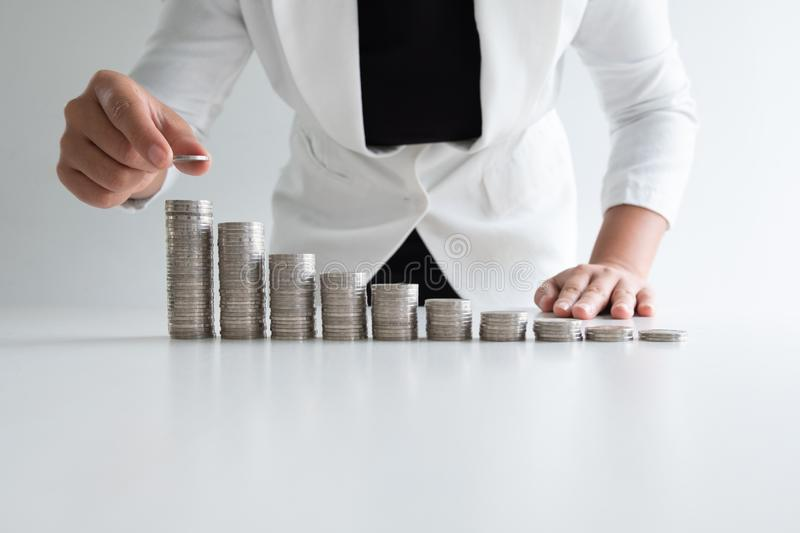 One woman putting coin on growth coins graph in white suit, step up growing business to success and saving for retirement concept royalty free stock photo