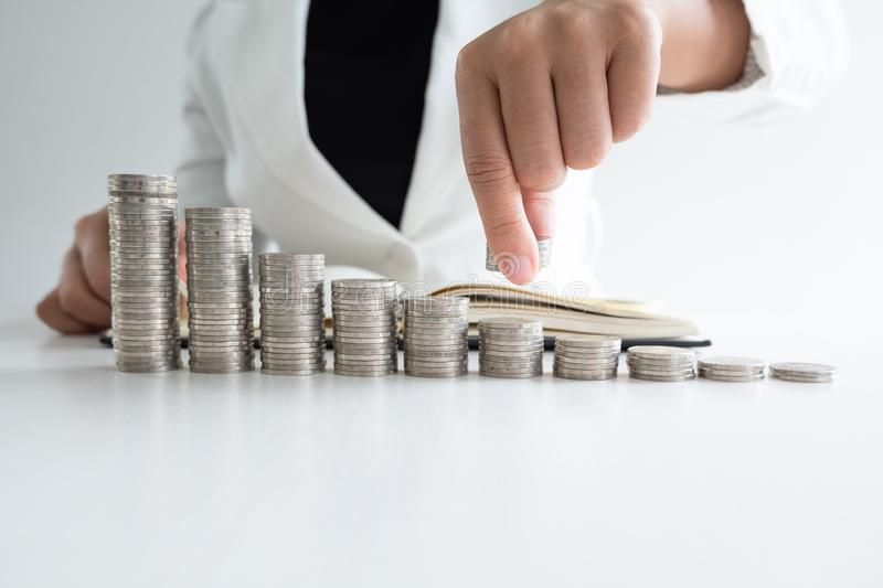 One woman putting coins on growth coins graph in white suit, step up growing business to success and saving for retirement concept stock images
