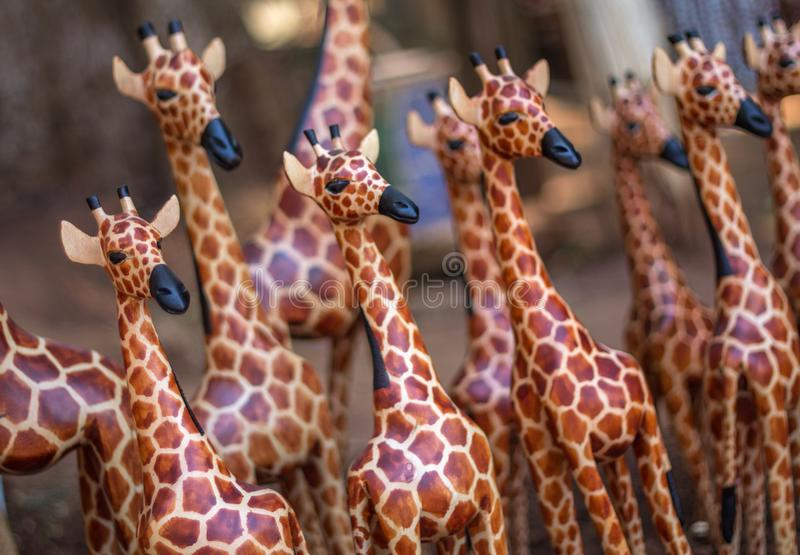 One wooden giraffe stands out in crowd of similar carvings royalty free stock photography