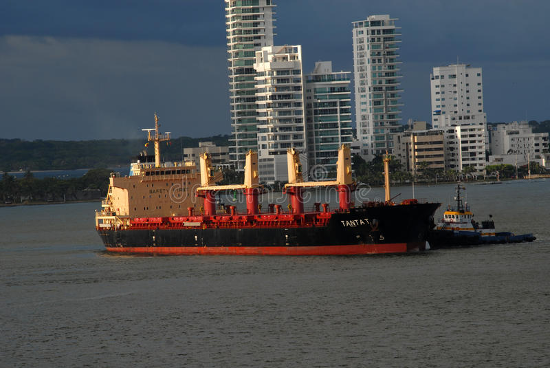 One of the working tugboats moving an unloaded container ship stock images