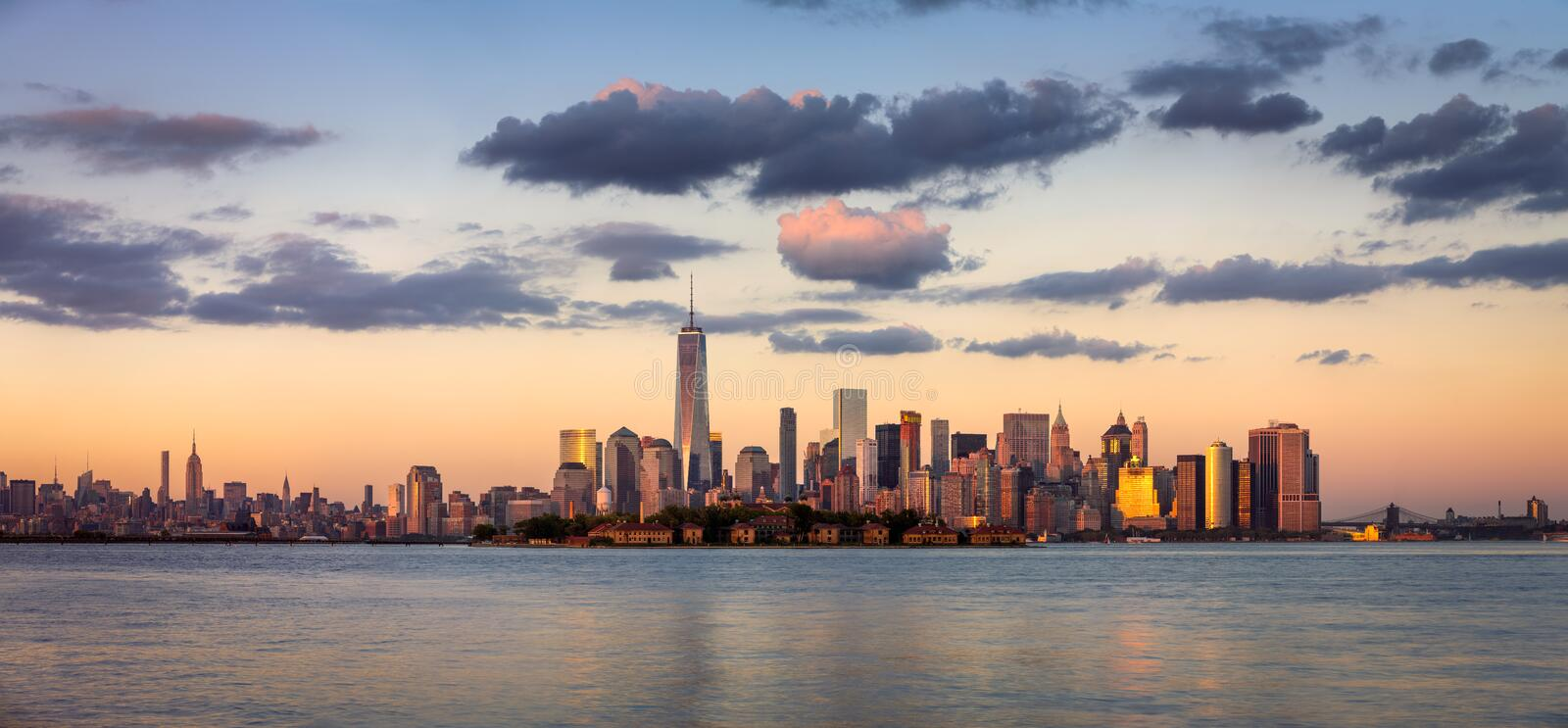One World Trade Center, Lower Manhattan at Sunset, New York. Lower Manhattan skyscrapers before sunset with One World Trade Center. Ellis Island appears in front royalty free stock image