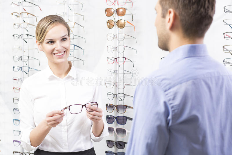These one would be pefect for you. Beautiful optometrist holding pair of glasses, talking with client royalty free stock images
