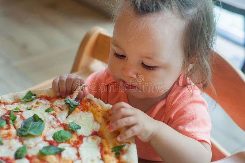 One Year boy sits in director chair in a public cafe indoor and eating italian pizza, children`s fast food. One Year boy sits in director chair in a public cafe stock image