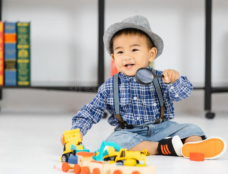 One year old Asian baby boy sitting on floor playing with toy royalty free stock photo