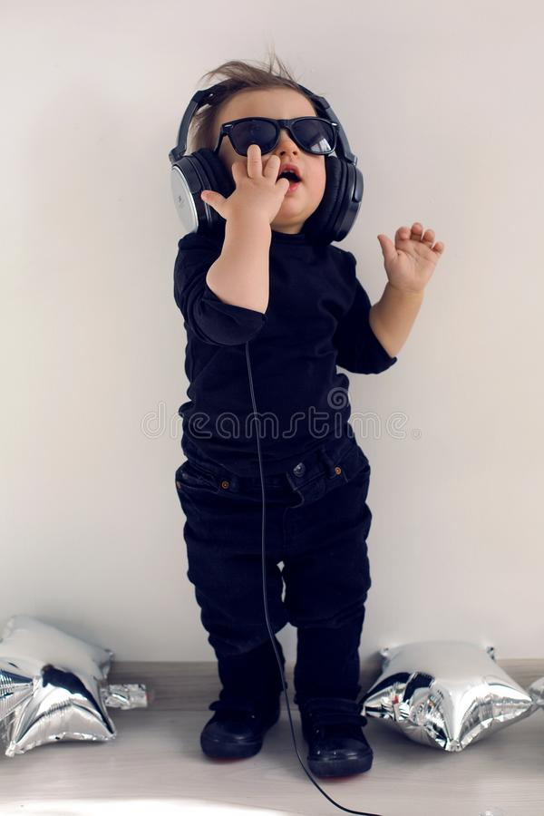 One-year-old baby in black clothes listening to rock music royalty free stock images