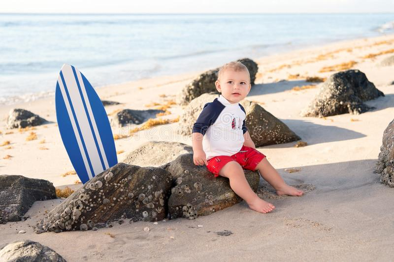 One Year Old Baby Boy at the Beach. A one year old baby boy sitting on a beach wearing swimwear royalty free stock photo
