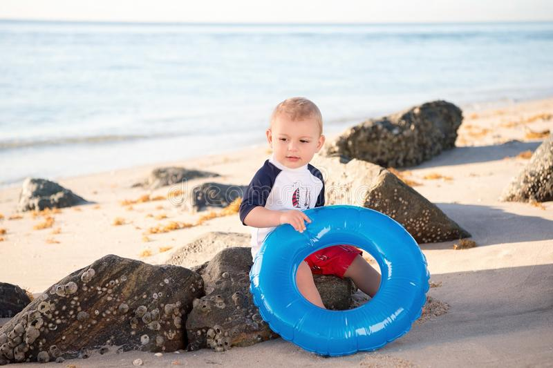 One Year Old Baby Boy at the Beach. A one year old baby boy sitting on a beach wearing swimwear royalty free stock image