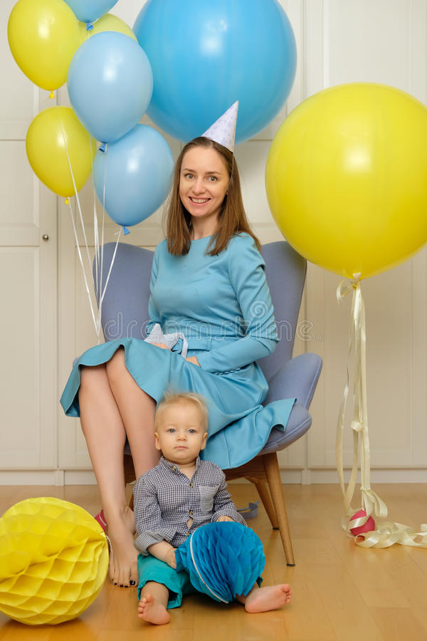 One year old baby boy first birthday. Toddler child with mother sitting in chair. And having fun with balloons royalty free stock image