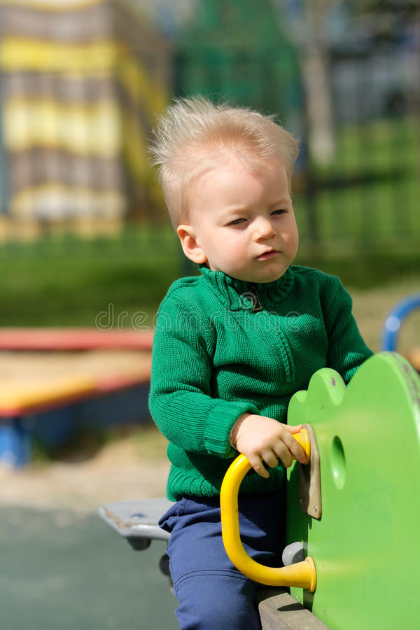 One year old baby boy toddler wearing green sweater at playground stock photography
