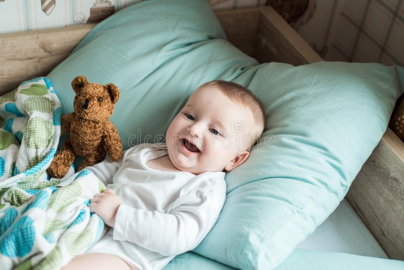 One year old baby lying in bed with a plush teddy bear royalty free stock photos