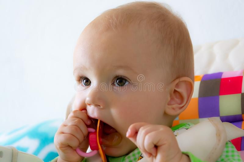 One year old baby nibbles / sucks on a rubber nipple because his teeth are being cut. Little cheerful boy in a light green suit wi stock image
