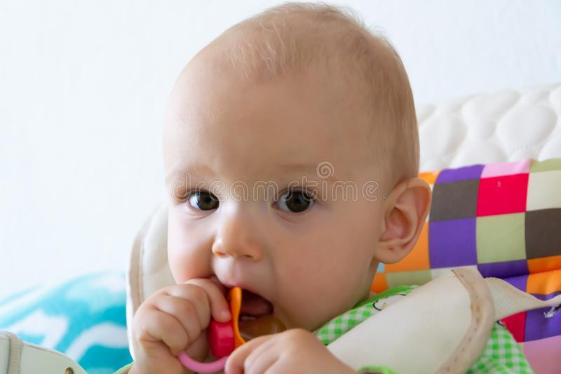 One year old baby nibbles / sucks on a rubber nipple because his teeth are being cut. Little cheerful boy in a light green suit wi royalty free stock photography