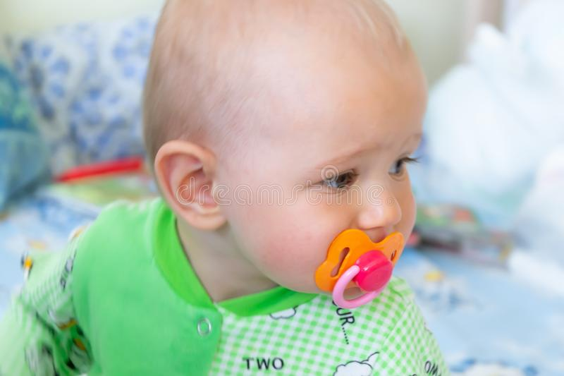 One year old baby nibbles / sucks on a rubber nipple because his teeth are being cut. Little cheerful boy in a light green suit wi. Th sheep. Soft focus, bokeh royalty free stock image