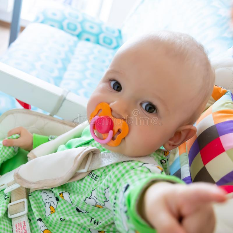 One year old baby nibbles / sucks on a rubber nipple because his teeth are being cut. Little cheerful boy in a light green suit wi. Th sheep.Soft focus, bokeh royalty free stock photography