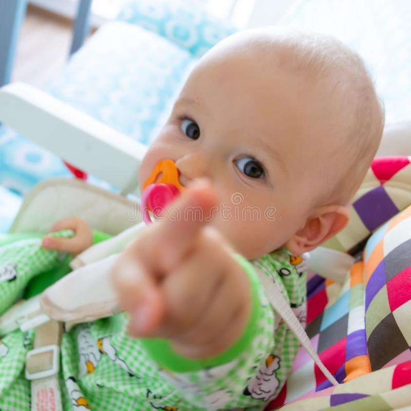 One year old baby nibbles / sucks on a rubber nipple because his teeth are being cut. Little cheerful boy in a light green suit wi. Th sheep.Soft focus, bokeh stock photography