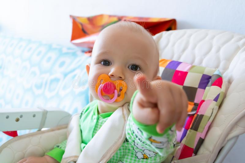 One year old baby nibbles / sucks on a rubber nipple because his teeth are being cut. Little cheerful boy in a light green suit wi. Th sheep. Soft focus, bokeh royalty free stock photography