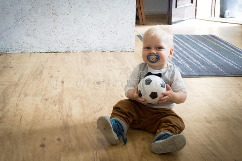 One year old boy with ball. An one year old boy sitting on a wood floor with a ball in hand royalty free stock images