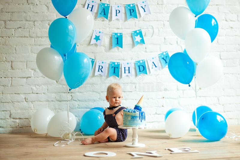 One year old boy is celebrating his first birthday among balloons and festive cake stock image