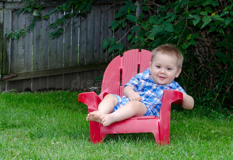 One year old boy in red chair stock photo