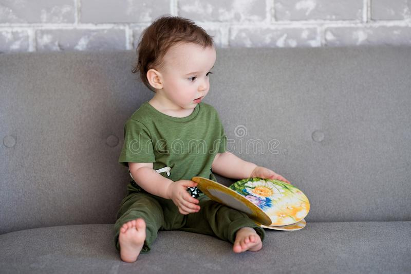 The one-year-old boy is sitting on a gray sofa with a book royalty free stock photos