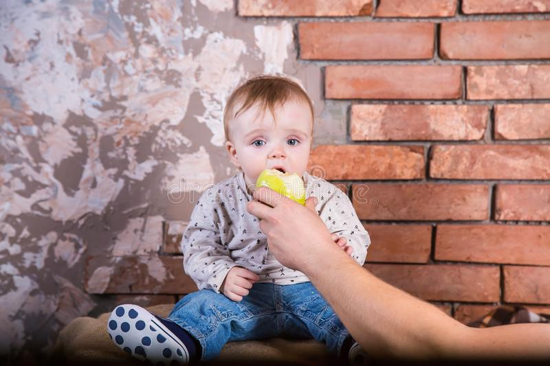 One year old child sits on a barrel against the background of a red brick wall and Ð¿oing to bite off a green apple which is held. By his father royalty free stock photo
