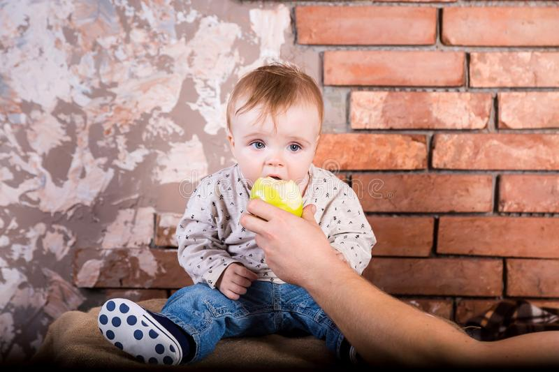One year old child sits on a barrel against the background of a red brick wall and bites off and eats a green apple which is held stock image