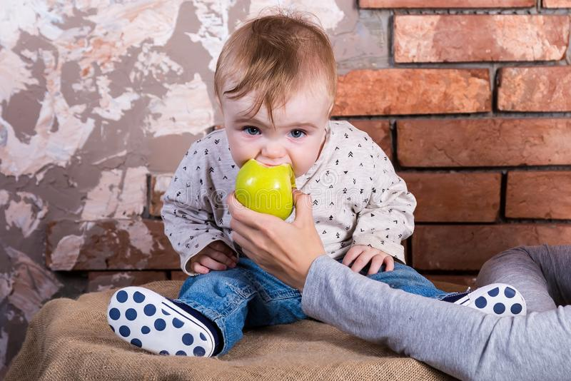 One year old child sits on a barrel against the background of a red brick wall and eats a green apple which is held by his mother.  royalty free stock photography