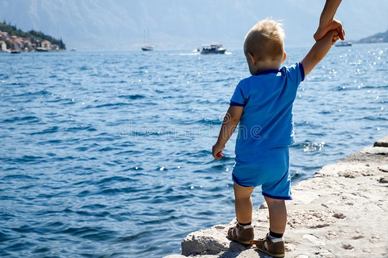One year old child stands on the edge of the pier and looks at the Bay of Kotor in Montenegro, view from the back royalty free stock photo