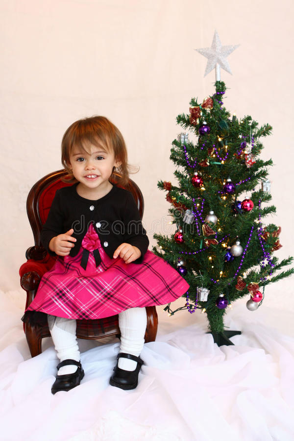 One year old Christmas toddler girl. A multicultural, Asian and Caucasian, one year old girl sits on a Victorian style chair, looking directly at the camera. She royalty free stock photography