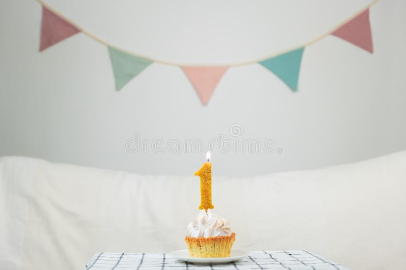One year old concept. `One` anniversary candle burning top of a little cake in decorated neat background stock photo