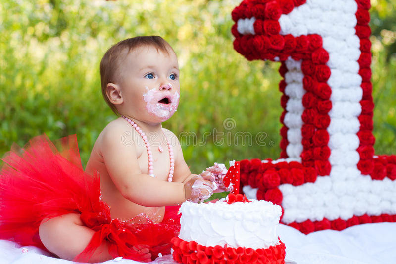One year old girl eating her first birthday cake stock photos