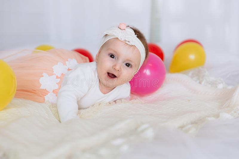 A one-year-old girl is lying on a white bed and laughing. A baby with brown eyes and a pink skirt plays with balloons at royalty free stock photo