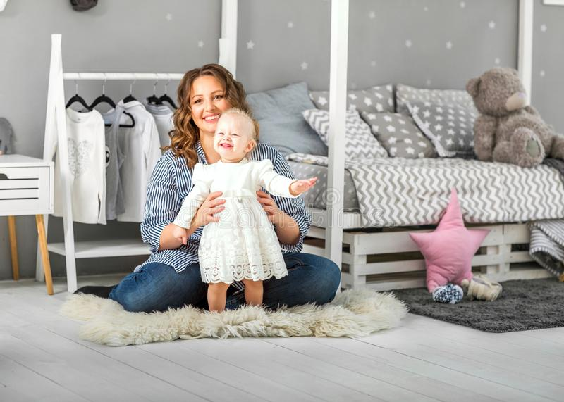 One year old girl playing near in the room with a toy horse, ska stock photo