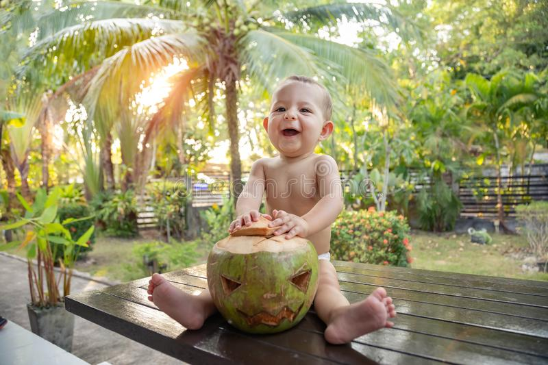 A one year old infant baby sits on a table against the background of palm trees and plays with a green coconut which is a symbol stock photography