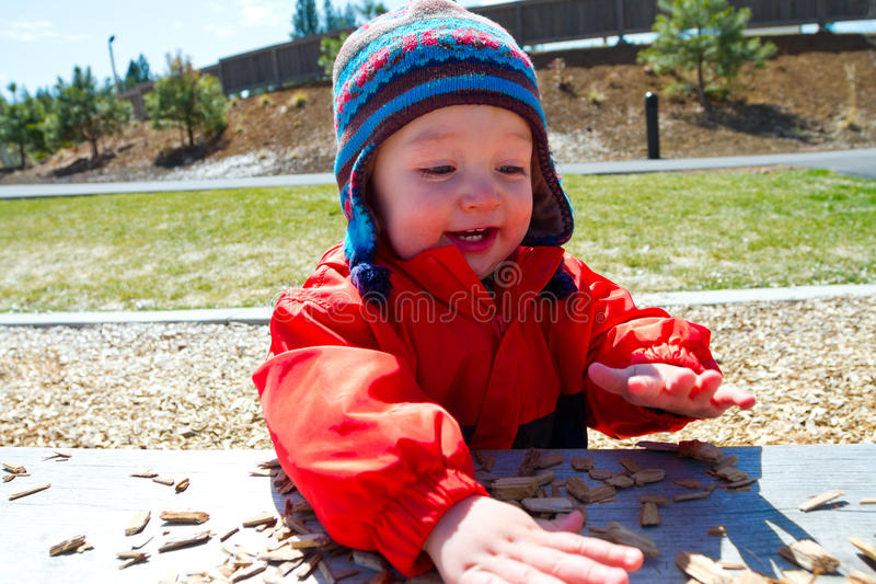 One Year Old Playing at Park. A one-year-old boy plays at a park outdoors with wood chips and structures to keep him entertained royalty free stock images