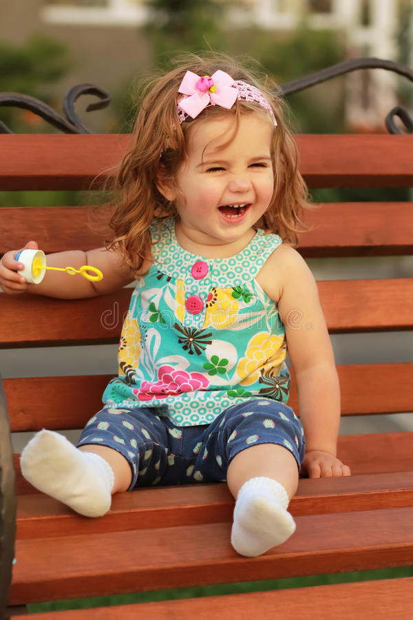 One year old sweet girl sitting on a wooden bench and laughing out load. In a lovely summer evening stock image
