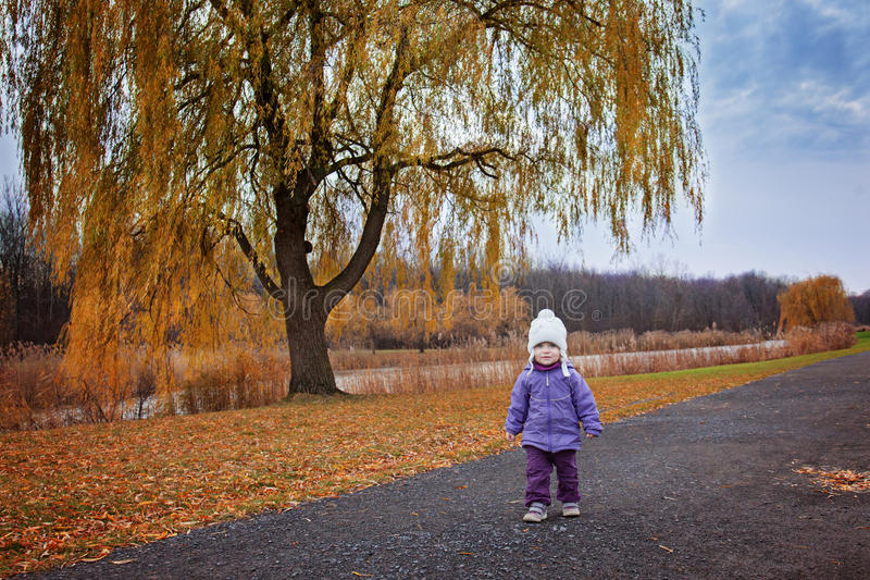 One year old toddler girl walking alone in the park royalty free stock image